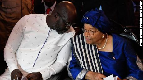 Liberia's president-elect and former football star George Weah (L) listens to the country's outgoing president Ellen Johnson Sirleaf during a church service at the centennial memorial pavilion in Monrovia on January 21, 2018, the eve of Weah's inauguration.