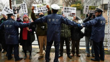 Protesters hold signs as police officers form a cordon during Tokyo's missile-attack drill Monday.