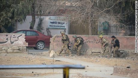 Afghan army soldiers take positions near an office of the British charity Save the Children during an ongoing attack in Jalalabad on January 24, 2018. Gunmen blasted their way into Save the Children's office in Afghanistan's restive east on January 24, 2018, witnesses and officials said, in an ongoing attack that has wounded at least 11 people. After blowing up a car outside the British charity's compound in Jalalabad city, the attackers used a rocket propelled grenade to storm the complex.  / AFP PHOTO / Noorullah SHIRZADA        (Photo credit should read NOORULLAH SHIRZADA/AFP/Getty Images)