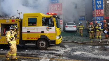 Firefighters work to put out the blaze Friday as smoke billows from the Sejong Hospital.