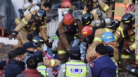 Rescue workers remove bodies from a hospital fire on Friday, January 26, in Miryang, South Korea.
