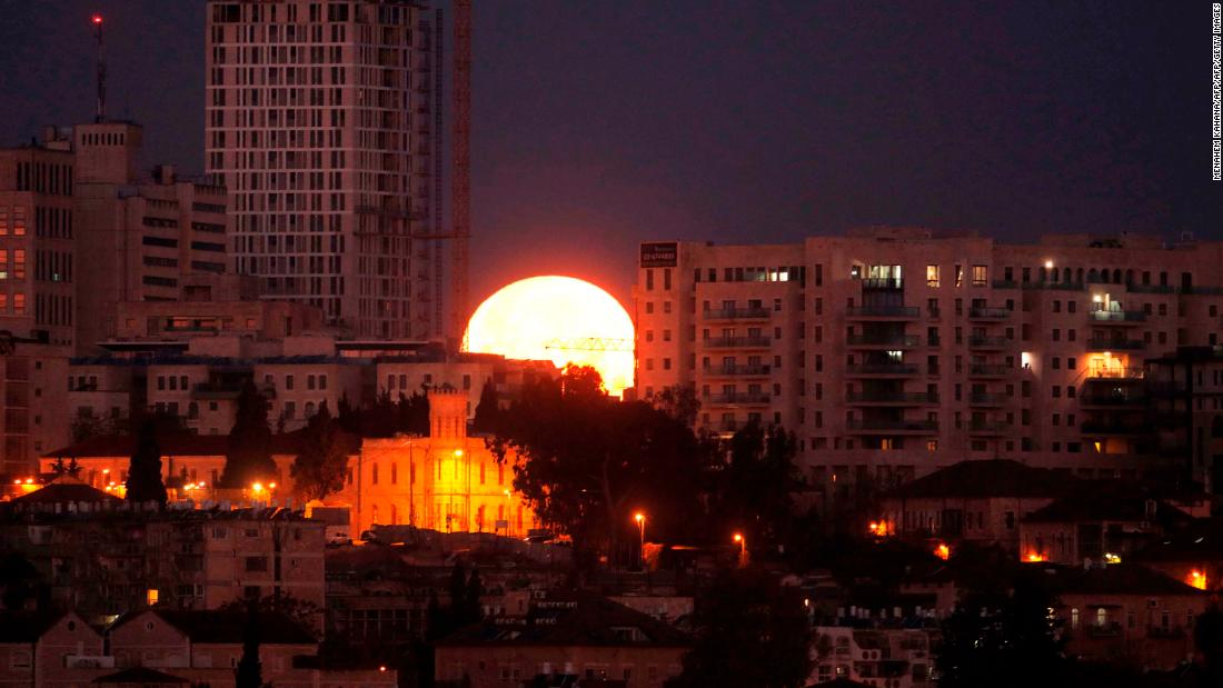 The supermoon sets behind buildings in Jerusalem.