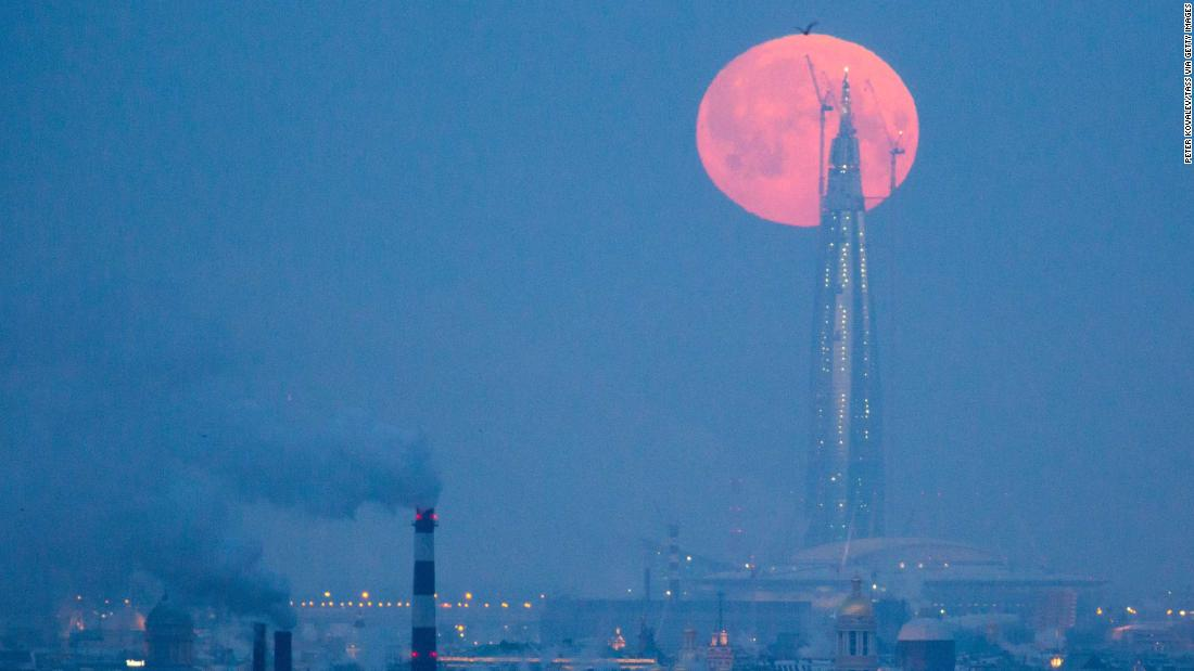 The supermoon passes over the tower of the Lakhta Center in St. Petersburg, Russia.