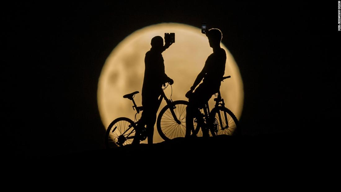 Bicyclists take photos of the supermoon in Lancelin, Australia.