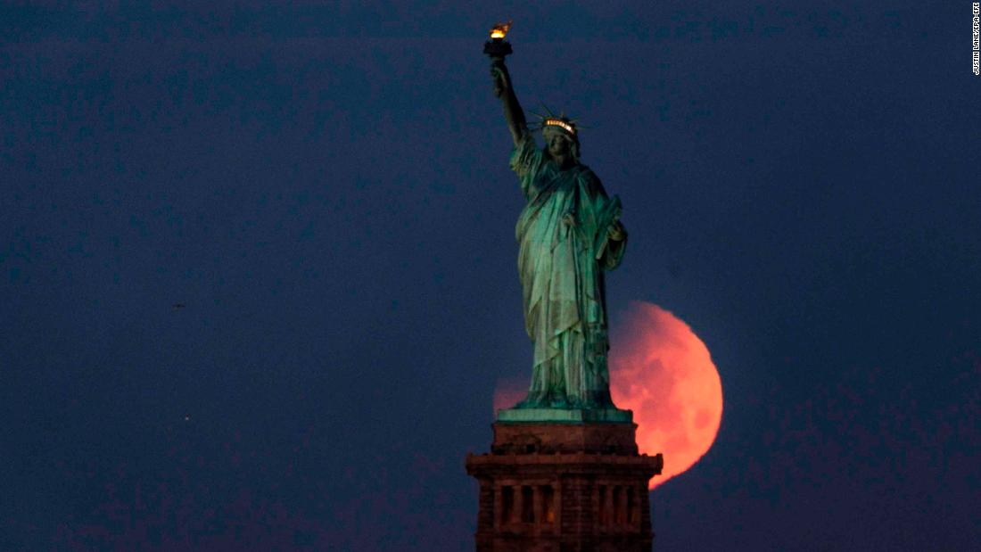 The supermoon sets behind the Statue of Liberty in New York.