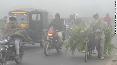 Indian commuters make their way through heavy smog in Amritsar in November 2017