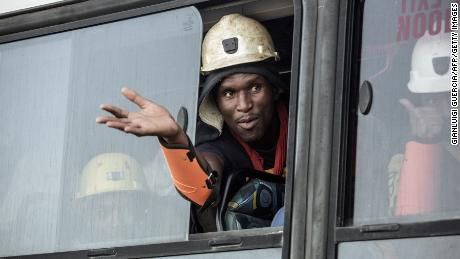 A rescued miner gestures out a bus window carrying some of the hundreds of miners rescued from the Beatrix gold mine shaft number 3 where nearly 1,000 miners were trapped underground following a power outage, in Theunissen on February 2, 2018. Hundreds of gold miners among almost a thousand trapped underground for more than a day in South Africa following a power-cut resurfaced on February 2, mining company Sibanye Gold said, as a rescue effort moved into full swing. / AFP PHOTO / GIANLUIGI GUERCIA        (Photo credit should read GIANLUIGI GUERCIA/AFP/Getty Images)