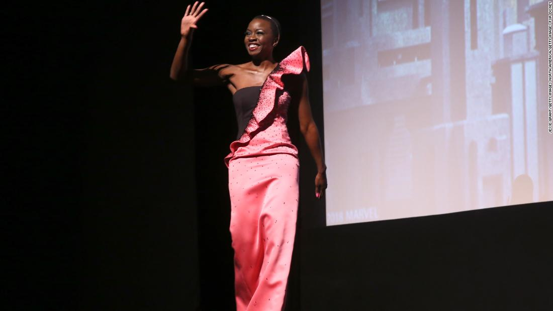 Danai Gurira is Okoye in Black Panther, head of Dora Milaje the all-female special forces of Wakanda. Gurira looked stunning in a silky pink dress with a ruffled sleeve running across the dress.