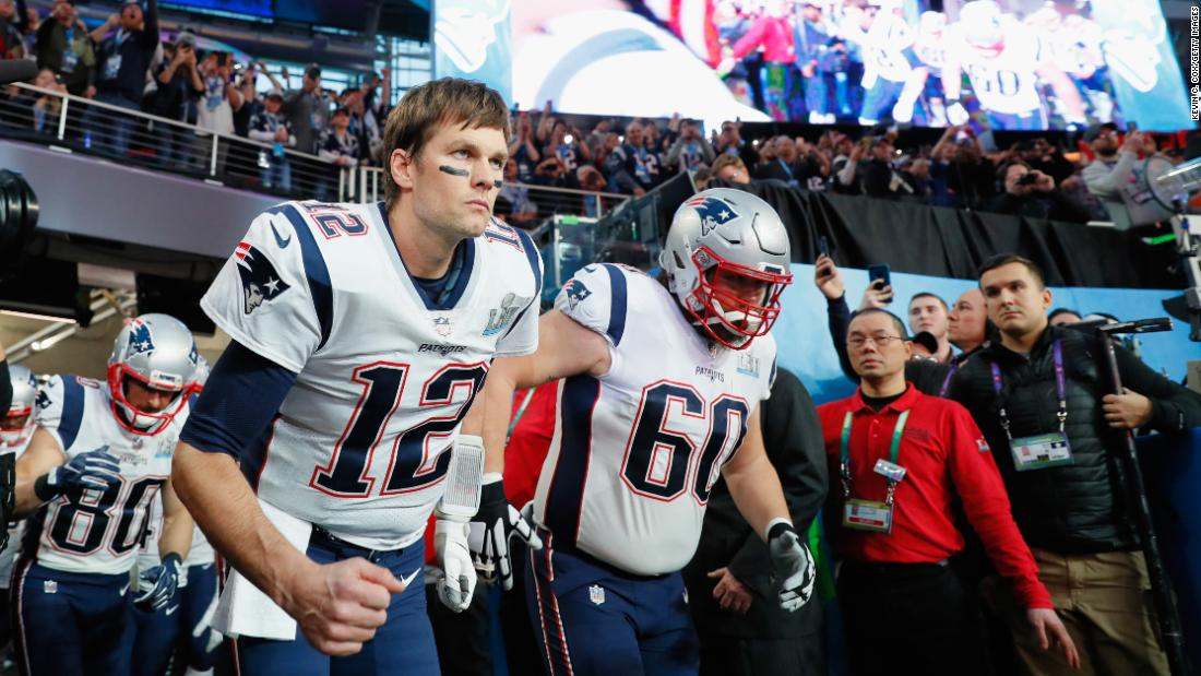 Brady and David Andrews (No. 60) lead the Patriots onto the field.