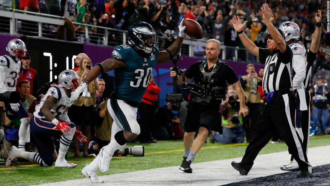 Philadelphia running back Corey Clement holds up the football after catching a 22-yard touchdown pass in the third quarter. The touchdown was held up after a video review, and Philadelphia took a 29-19 lead after the extra point.