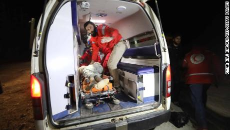 Syrian emergency services treat a victim rescued from a collapsed building after airstrikes on Idlib.