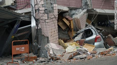 A car sits crushed under a building Wednesday after a 6.4 magnitude quake hit in Hualien.
