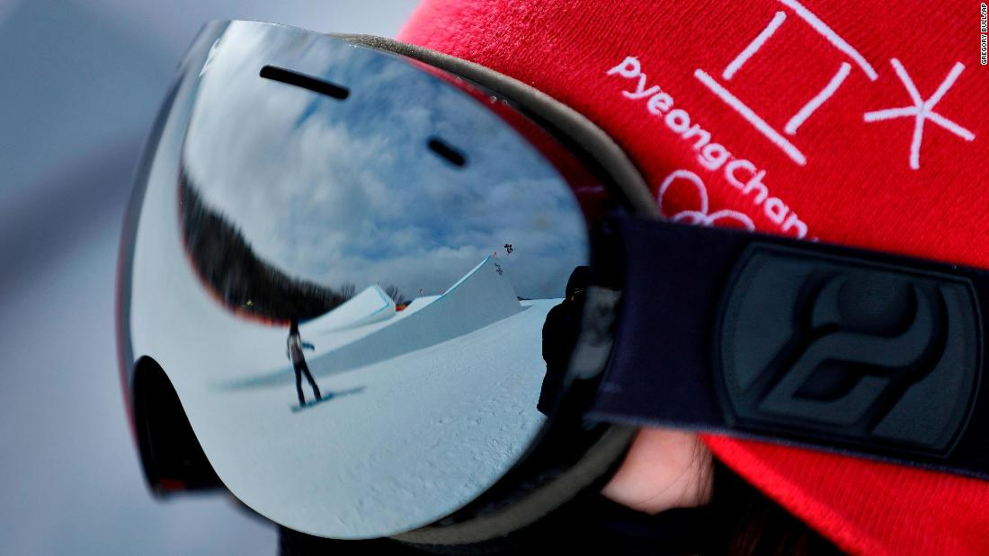 A volunteer watches as athletes run the course during a training session prior to the women's slopestyle qualifying.
