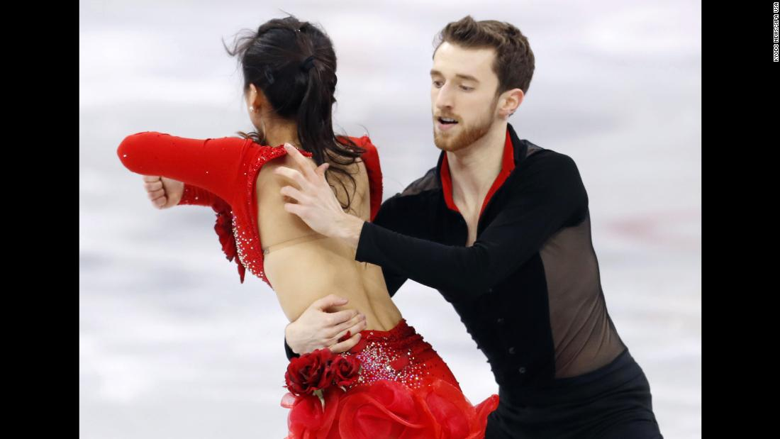 Alexander Gamelin attempts to fix the outfit of partner Yura Min during their ice dance performance.