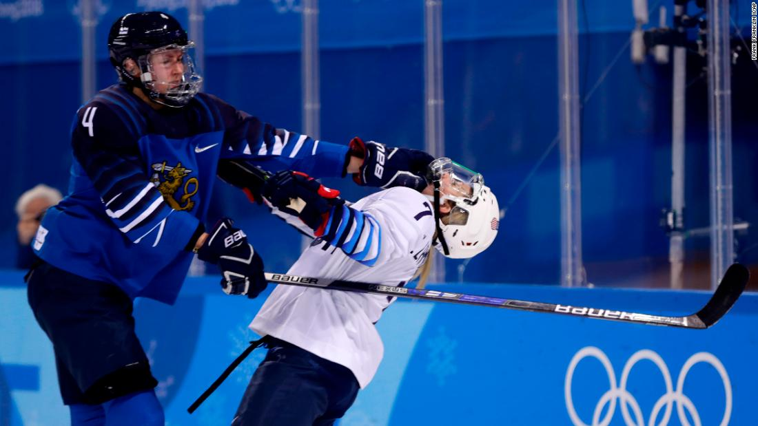 Monique Lamoureux-Morando of the United States, takes a punch from Rosa Lindstedt of Finland, during the preliminary round of the women's ice hockey.