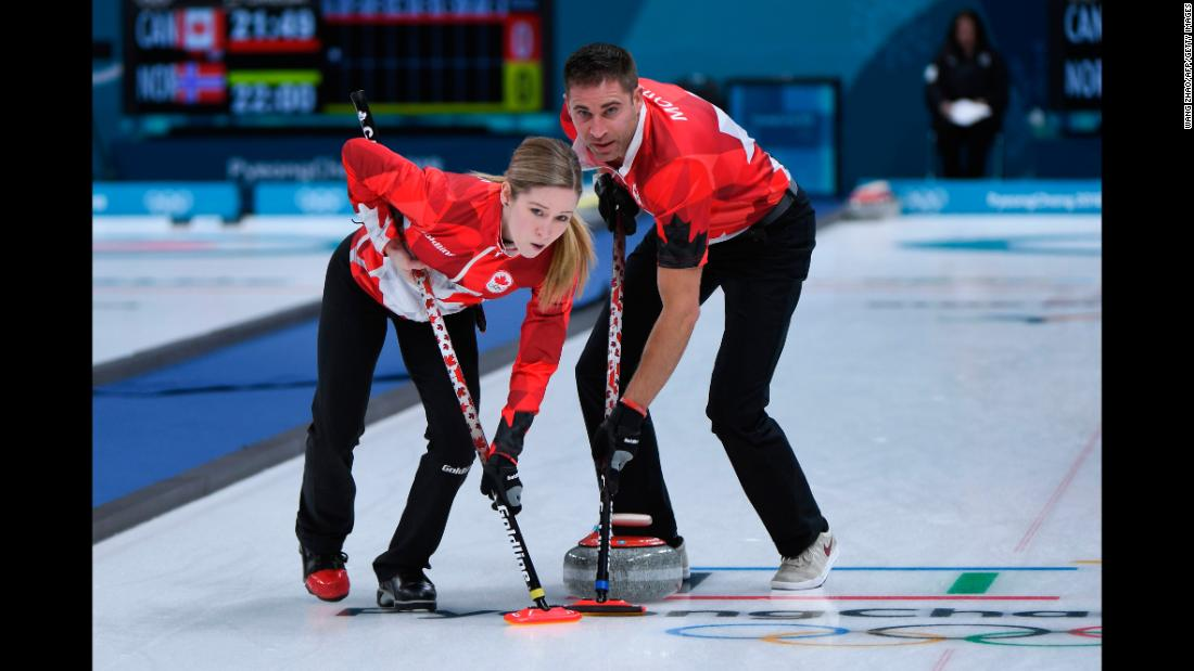 Canada's Kaitlyn Lawes and John Morris brush the ice during a curling match.