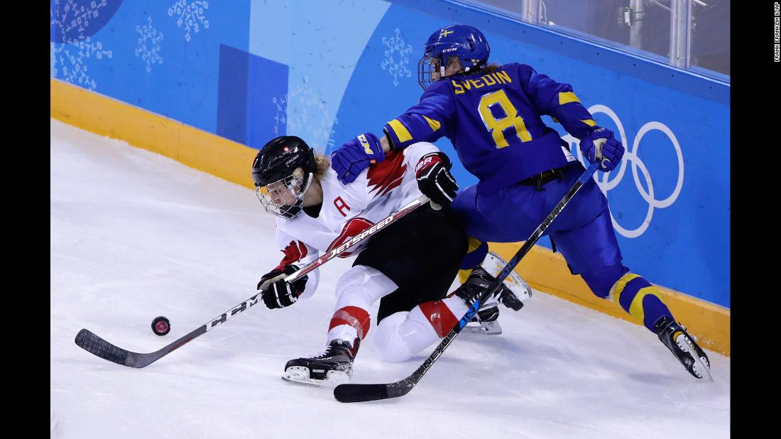 Switzerland's Lara Stalder, left, and Sweden's Annie Svedin battle for the puck during a preliminary-round hockey game.