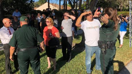 Parents confer with security following a shooting at Marjory Stoneman Douglas High School in Parkland, Florida, a city about 50 miles (80 kilometers) north of Miami, February 14, 2018 .