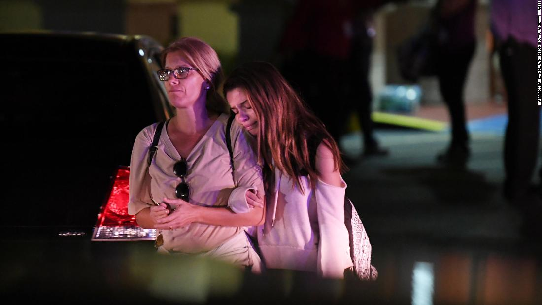People embrace while leaving the Fort Lauderdale Marriott Coral Springs Hotel, which authorities designated as a staging point for witnesses to the shooting.