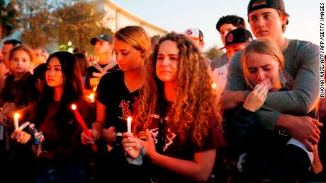 Mourners react during a candlelight vigil for the victims of Marjory Stoneman Douglas High School shooting in Parkland, Florida on February 15, 2018.A former student, Nikolas Cruz, opened fire at the Florida high school leaving 17 people dead and 15 injured. / AFP PHOTO / RHONA WISE        (Photo credit should read RHONA WISE/AFP/Getty Images)