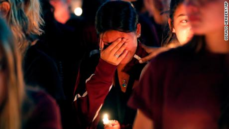 A woman cries during a candlelight vigil for the victims of the Wednesday shooting at Marjory Stoneman Douglas High School, in Parkland, Fla., Thursday, Feb. 15, 2018. Nikolas Cruz, a former student, was charged with 17 counts of premeditated murder on Thursday. (AP Photo/Gerald Herbert)