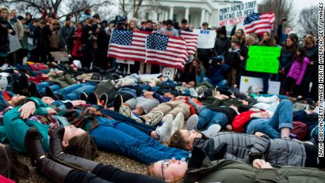 "WASHINGTON, DC - FEBRUARY 19: Demonstrators lie on the ground a ""lie-in"" demonstration supporting gun control reform near the White House on February 19, 2018 in Washington, DC.  According to a statement from the White House, ""the President is supportive of efforts to improve the Federal background check system."", in the wake of last weeks shooting at a high school in Parkland, Florida. (Photo by Zach Gibson/Getty Images)"
