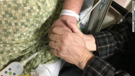 Steve Melanson holds his wife's hand while she was hospitalized after the Las Vegas shooting.