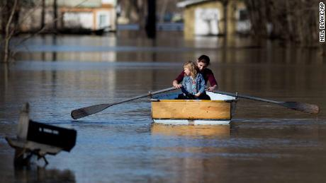 Emily Snyder teaches her daughter, Skyler, 4, how to row a boat as they check out their flooded home in Plainfield Township, Michigan, on Monday.