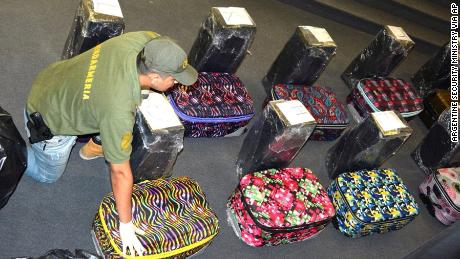 A police officer guards the suitcases found carrying the drugs.