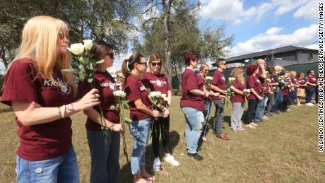 Parkland parents, students and community members hold flowers at the Pulse nightclub attack site.