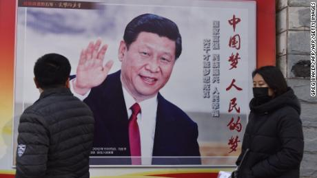 People walk past a poster of Chinese President Xi Jinping beside a street in Beijing on February 26, 2018.