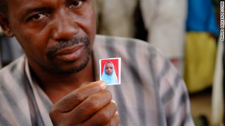 Alhaji Garba Tela shows a photograph of his missing daughter, Zainab.