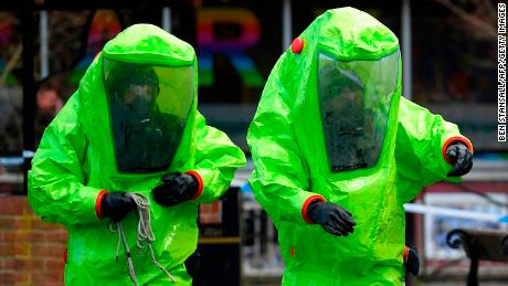 Investigators in biohazard suits at the bench where 