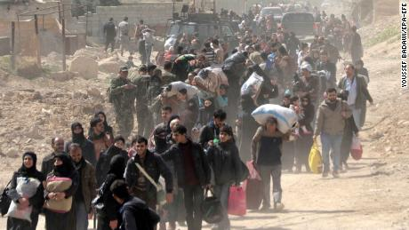 epa06605665 Hundreds of civilians leave rebels-held Eastern Ghouta in the countryside of Damascus, Syria, 15 March 2018. According to Syrian official media reports, the Syrian Arab Army secured the exit of at least 10 thousand civilians from the town of Hamoria in Eastern Ghouta through the newly opened al-Baz corridor. On 19 February 2018 the Syrian government started a military campaign to regain control of rebels-held Eastern Ghouta in Damascus's countryside. Around 1500 civilians were killed according to local reports.  EPA-EFE/YOUSSEF BADAWI
