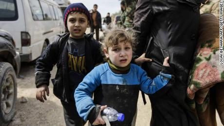 A Syrian girl and boy from the Eastern Ghouta enclave walk with another woman and civilians through the regime-controlled corridor opened by government forces in Hawsh al-Ashaari, east of the enclave town of Hamouria on the outskirts of the capital Damascus on March 15, 2018.