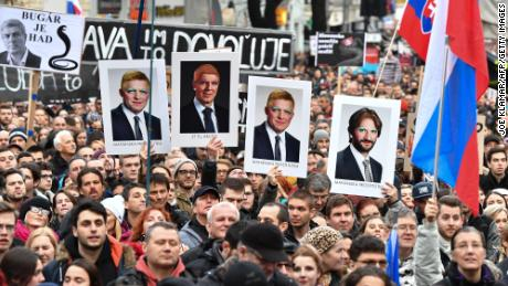 "Protesters holds placards bearing faceted portraits of Slovakia's Prime Minister Robert Fico (L and 2R) and Interior Minister Robert Kalinak (R) near the Slovak National Uprising (SNP) square during a rally under the slogan ""For a Decent Slovakia"", against corruption and to pay tribute to murdered Slovak journalist Jan Kuciak and his fiancee Martina Kusnirova on March 16, 2018 in Bratislava, Slovakia. Organisers of the anti-government street protests this month continue to call for snap elections as well as a thorough and independent investigation of the journalist murder."
