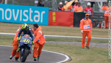 Valentino Rossi is helped back onto his bike after crashing out.