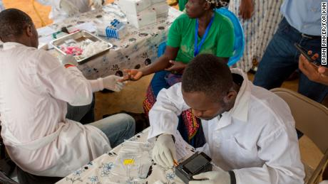 Researchers test the latest version of the LoaScope in a village in Cameroon.