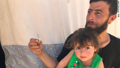 "Walid Dervish, 23, pictured with his daughter, says he brought his Douma house keys with him to the refugee camp. ""Maybe one day I can go back,"" he said."