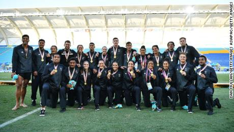 New Zealand men and women's team pose with their gold medals following their wins.