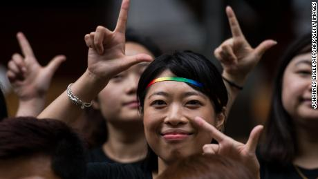 Runners in the 2016 Shanghai Pride Run make signs with their fingers while wearing rainbow shoelaces at the start of the race.