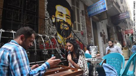 Egyptians gather at a cafe near a graffiti of Salah in Cairo on March 22, 2018.
