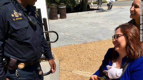 Democratic Sen. Tammy Duckworth of Illinois holds two United States Capitol Police baby stickers that were given to her for Take Your Child to Work Day.
