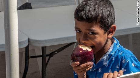 Omar eats an apple. It's been hard for the family to get enough nutritious food.