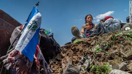 The family sits on top of a load of trash being carried on a freight train taking them north.
