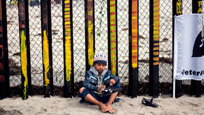 "A Central American migrant boy travelling in the ""Migrant Via Crucis"" caravan removes sand of his shoes during a demonstration at the US/Mexico Border at Tijuana's beaches, Baja California state, Mexico, on April 29, 2018. - The US has threatened to arrest around 100 Central American migrants if they try to sneak in from the US-Mexico border where they have gathered, prompting President Donald Trump to order troop reinforcements on the frontier. (Photo by GUILLERMO ARIAS / AFP)        (Photo credit should read GUILLERMO ARIAS/AFP/Getty Images)"