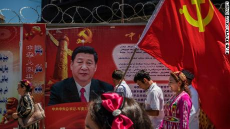 Ethnic Uyghur members of the Communist Party of China carry a flag past a billboard of Chinese President Xi Jinping as they take part in an organized tour on June 30, 2017 in the old town of Kashgar, Xinjiang.