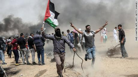 "TOPSHOT - Palestinian protesters pull a metal cable as they try to take down a section of barbed wire during clashes with Israeli forces on April 20, 2018, east of Khan Yunis, in the southern Gaza Strip during mass protests along the border of the Palestinian enclave, dubbed ""The Great March of Return,"" which has the backing of Gaza's Islamist rulers Hamas. (Photo by SAID KHATIB / AFP)        (Photo credit should read SAID KHATIB/AFP/Getty Images)"
