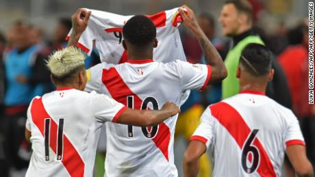 Peru's Raul Ruidiaz, Jefferson Farfan and Miguel Trauco hold aloft Guerrero's jersey during his absence.
