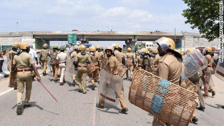 Indian police officials run towards protesters on Tuesday.